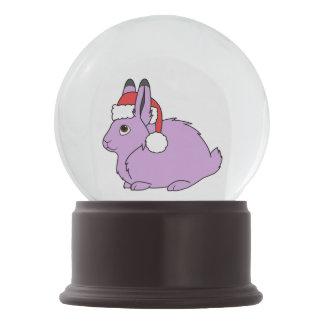 サンタの赤い帽子が付いている薄紫の北極ノウサギ スノーグローブ