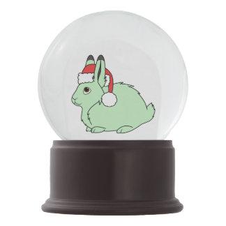 サンタの赤い帽子が付いている薄緑の北極ノウサギ スノーグローブ