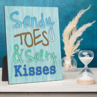 サンディのつま先および塩辛いキスは青、水の印を浜に引き上げます フォトプラーク