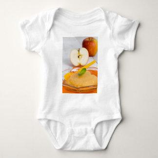 シナモンおよびオレンジスプーンが付いているアップルソース ベビーボディスーツ