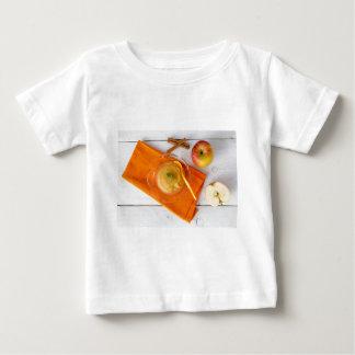 シナモンおよびオレンジスプーンが付いているアップルソース ベビーTシャツ