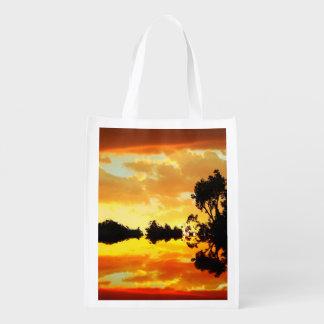 シルエットを描かれる湖の木に反映されるオレンジ日没 エコバッグ