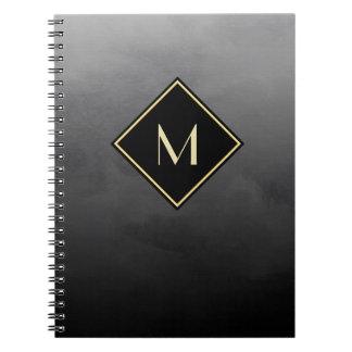 シンプルな金ゴールドのモノグラムとのエレガントなブラシをかけられた黒 ノートブック
