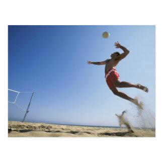 スパイクまで跳んでいるオスのビーチバレープレーヤー ポストカード