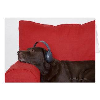 ソファーにあるラブラドールの身に着けているヘッドホーン グリーティングカード