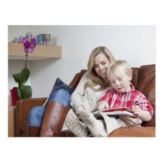 ソファーに一緒に坐っている母および息子 葉書き