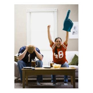 ソファーの監視フットボールに坐っている人および女性 ポストカード