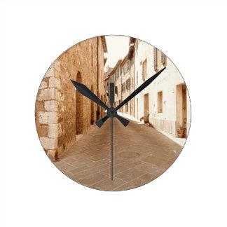 タスカニーの古い村の細道。 Pienza、イタリア ラウンド壁時計