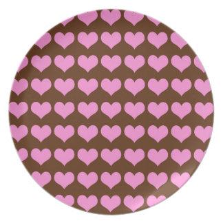 チョコレート色の背景のカラフルなピンクのハート プレート