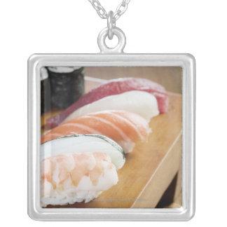 テーブルの寿司のクローズアップ シルバープレートネックレス