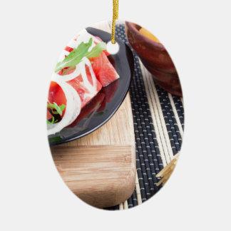 トマト、タマネギの新しいサラダが付いているブラックプレート セラミックオーナメント