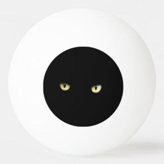 ハロウィンの黒猫はピンポン球を注目します 卓球ボール