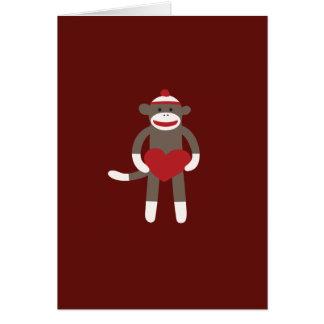 ハートを保持する帽子を持つかわいいソックス猿 グリーティングカード