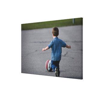 バスケットボールのアウトドアを追跡している男の子 キャンバスプリント