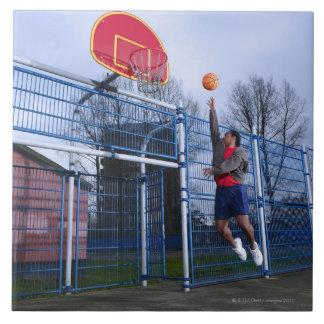 バスケットボールのアウトドアを遊んでいる若者 タイル