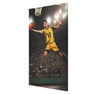バスケットボールを跳び、保持している若者 キャンバスプリント