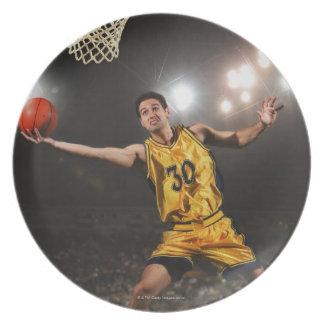 バスケットボールを跳び、保持している若者 プレート