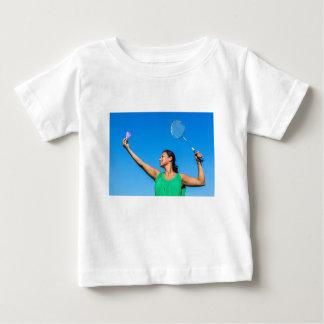 バドミントンラケットとのコロンビアの女性のサーブ ベビーTシャツ