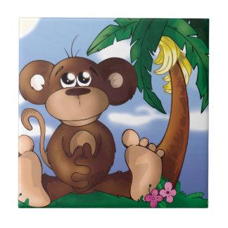 バナナの木の隣に坐っているかわいく小さい猿 タイル
