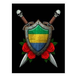 バラが付いている擦り切れたなガボンの旗の盾そして剣 ポストカード
