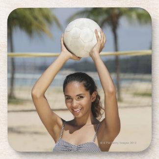 バレーボールを保持していたりおよびで微笑している若い女性 コースター