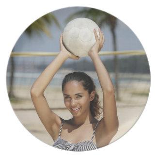 バレーボールを保持していたりおよびで微笑している若い女性 プレート