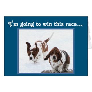 バースデー・カードのお誕生日ケーキのために競争しているバセット犬 カード