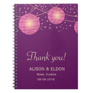 パステル調の暗い紫色のお祝いのランタン及びピンク ノートブック