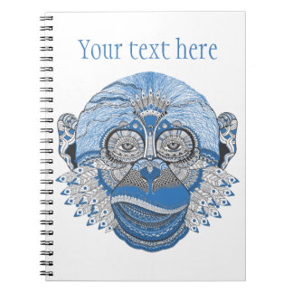 パターンおよび羽が付いている青い猿の顔 ノートブック