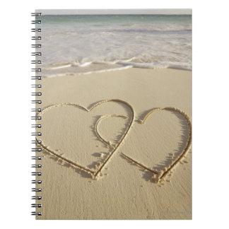 ビーチでとの描かれる2つの重なるハート ノートブック