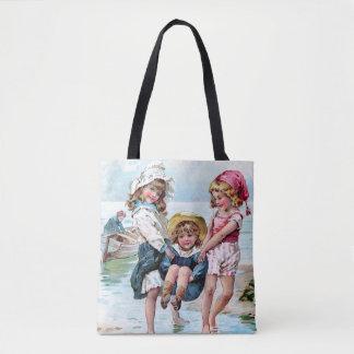 ビーチで遊んでいる3人の小さな女の子 トートバッグ