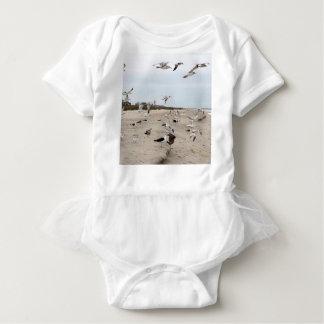ビーチで飛び、立ち、そして食べているカモメ ベビーボディスーツ