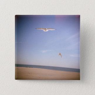 ビーチで飛んでいるカモメの夢みるようなイメージ 5.1CM 正方形バッジ