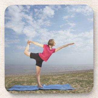 ビーチによる女性の練習のヨガ コースター