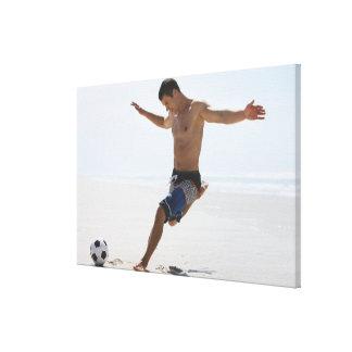 ビーチのサッカーボールを蹴っている人 キャンバスプリント