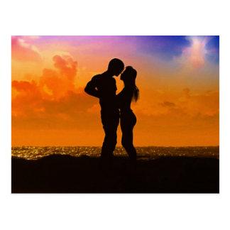 ビーチの日没で接吻している恋人 ポストカード