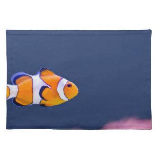 ピエロの魚はピンクのアネモネが付いている青海原で泳ぎます ランチョンマット
