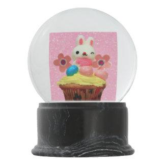 ピンクのカップケーキのバニーの雪の地球 スノーグローブ