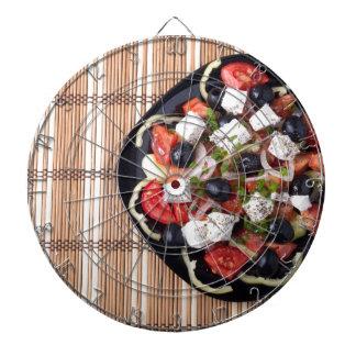 ブラックプレートの菜食主義サラダの平面図 ダーツボード