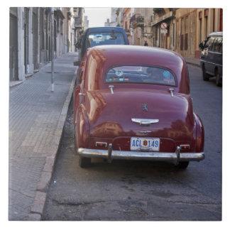 プジョークラシックで古く赤い車は通りで駐車しました タイル