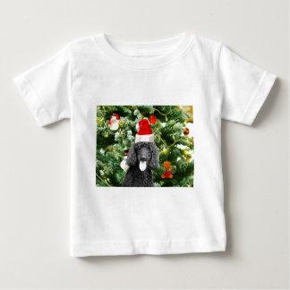 プードル犬のクリスマスツリーの雪だるまの赤いサンタの帽子 ベビーTシャツ