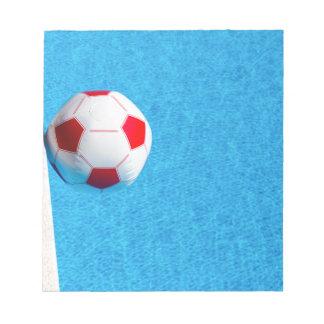 プールで浮かぶ赤白のビーチボール ノートパッド