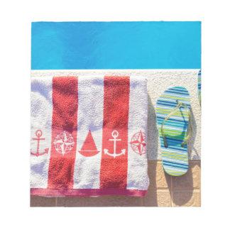 プールのスリッパそして浴室タオルを浸すこと ノートパッド