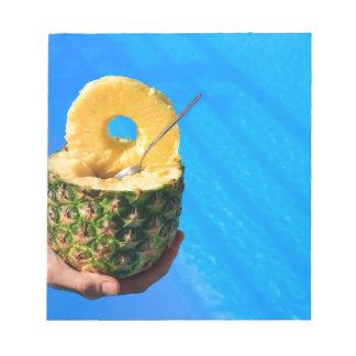 プールの上の新しいパイナップルを握る手 ノートパッド