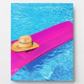 プールの帽子が付いているピンクの空気mattrass フォトプラーク