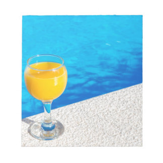 プールの端のオレンジジュースが付いているガラス ノートパッド