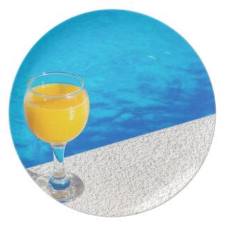 プールの端のオレンジジュースが付いているガラス プレート