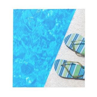 プールの端の2つの浸るスリッパ ノートパッド