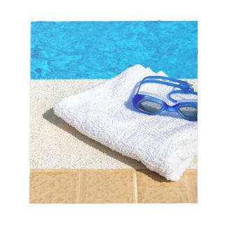 プールの近くの水泳ゴーグルそしてタオル ノートパッド