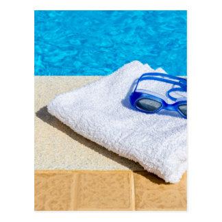 プールの近くの水泳ゴーグルそしてタオル ポストカード